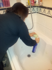 Cardiff Home Cleaner cleaning a bath and tiles
